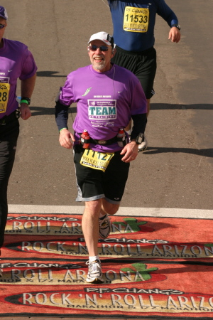 Tom Gilbert crossing the finish line of a marathon