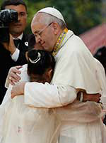 Pope Francis embraces a teenager