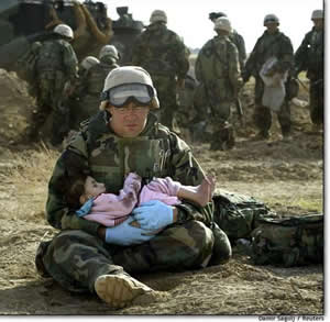 A soldier with child in Iraq - photo by Damir Sagolj / Reuters News Service